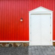 Red wooden wall and white front doors with two lamps — Stock Photo #36455475