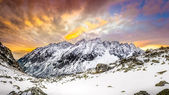 Panoramic view of white winter mountains after colorful sunset — Stock Photo