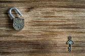Open vintage hangslot en de sleutel op een houten structuur — Stockfoto