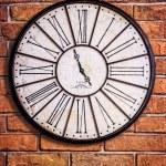 Old vintage clock on textured brick wall — Stock Photo #40635531