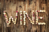 Sign wine made from corks on wooden vintage table — Stock Photo