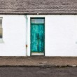 Green door and two windows on white wall house — Stock Photo