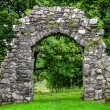Old stone entrance wall in green garden — Stock Photo