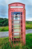 Detail of old red English phone booth in countryside — Stock Photo