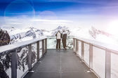 Two people looking at Alps mountains from viewpoint platform — Stock Photo