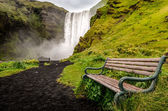 Landscape view of wild Skogafoss waterfall and bench — Stock Photo