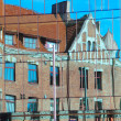 Reflection of old house in glass of new building - Stock Photo