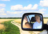 Young couple in car at countryside — Stock Photo
