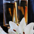 Glasses with wine and lily flower on black silk - Stock Photo