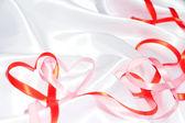 Red ribbon hearts — Stock Photo