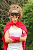 Blond dziewczyna nosi jednolity czerwony superbohatera i czarna maska uśmiechający się — Zdjęcie stockowe