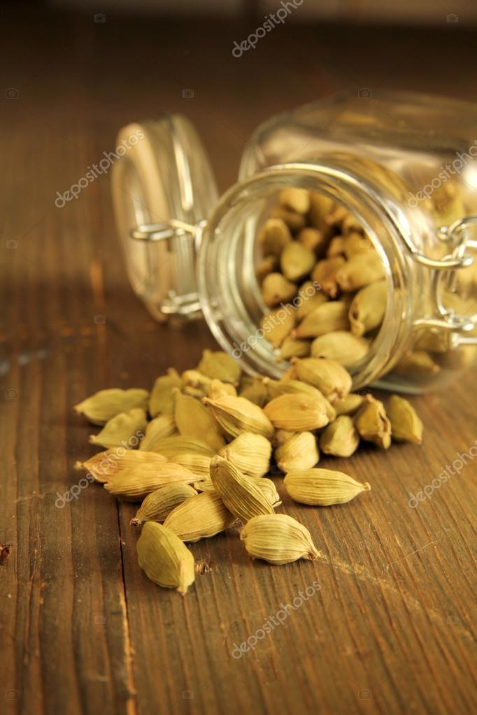 Cardamom in a jar on a wooden table — Stock Photo #13746494
