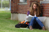 GIrl sit in a grass and study — Stock Photo