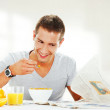 Happy young man reading newspaper while having energetic breakfa — Stock Photo