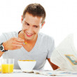 Happy young man reading newspaper while having energetic breakfa — Stock Photo #12816882