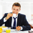 Happy businessman having breakfast at office — Stock fotografie