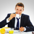 Photo: Happy businessman having breakfast at office