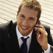 Happy young businessman calling with mobile phone — Stock Photo #12817096