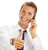 Smiling young business man talking on the phone and making ok — Stock Photo