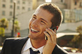 Happy young businessman calling with mobile phone — Stock Photo