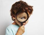 Niño mirando a través de una lupa — Foto de Stock