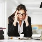 een jonge zakenvrouw is op zoek benadrukt als ze op haar computer werkt — Stockfoto