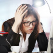 A young businesswoman is looking stressed as she works at her computer — Foto de Stock