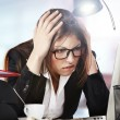 A young businesswoman is looking stressed as she works at her computer - Stock Photo