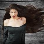 长的黑发姑娘的头发,飞过木背景 — 图库照片 #13604982