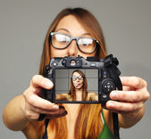 Beautiful young woman taking a picture and sticking out her tongue — Stock Photo
