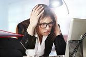 En ung affärskvinna ser stressad som hon arbetar på sin dator — Stockfoto