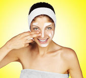 Beautiful young woman applying a creme on her face - on yellow background — Stock Photo