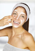 Beautiful young woman applying a creme on her face isolated on bathroom bac — Stock Photo