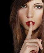 Portrait of attractive young girl with finger on lips, brown long hair, iso — Stock Photo