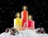Drie Kerst kaarsen en dennenappels in een sneeuw-achtergrond. — Stockfoto