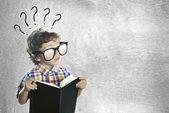 Kind mit einem buch auf der suche nach antworten — Stockfoto