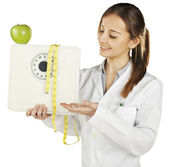 Nutritionist showing a weight scale and green apple — Stock Photo