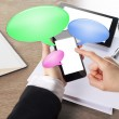 Young businesswoman working on smart phone with chat bubble icon — Stock Photo
