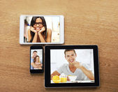Digital tablets and smart phone with images on a desktop — Stock Photo