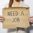 Young business woman holding a poster that says need a job — Stock Photo #19737597