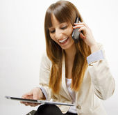 Happy business woman talking on smart phone and working on digital tablet — Stock Photo