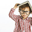 Stock Photo: Child who wears plaid shirt with a book on his head