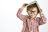 Child who wears plaid shirt with a book on his head — Stock Photo