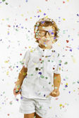 Smiling child with rimmed glasses and confetti — Stock Photo