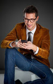 Young interesting businessman touching smartphone — Stock Photo