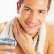 Young man applying after shave — Stock Photo #21612811