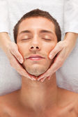 Young man receiving facial massage — Stock Photo
