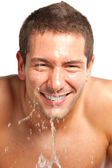 Young man spraying water on his face after shaving in the bathroom — Stock Photo