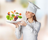 Happy cook woman holding a dish with floating vegetables on the kitchen — Stock Photo