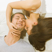 Young couple lying and his girlfriend kissing — Stock Photo